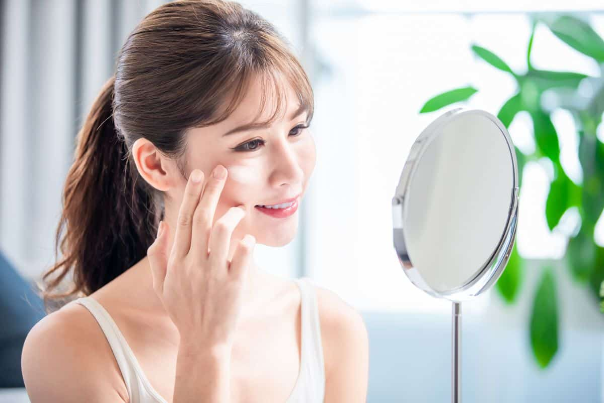 asian young woman look in mirror and apply whitening cream on her face