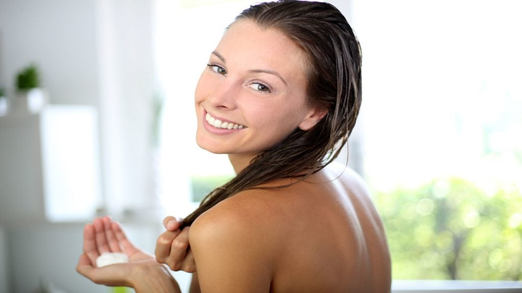 woman putting on hair conditioner