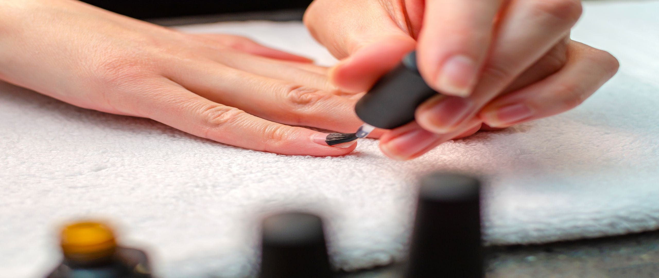 A woman applies a primer to her nails before applying varnish